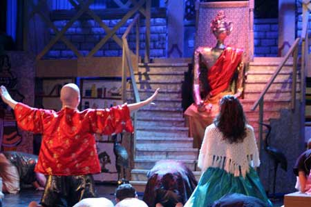 The King (junior Brad Witucki) praying to Buddha for guidance as Anna (senior Elaina Daoulas) watches