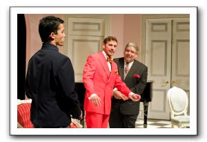 Jacob Yeh, left, and Lucas Beck, center, as master and servant who have switched places, with their host, Jon Johnson