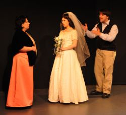 Benjamin Braddock (Zachary Hamilton) attempts to kidnap Elaine (Heather Martin) from her wedding, while Mrs Robinson (Rachel Duda) intervenes.