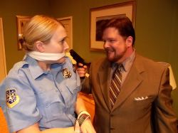 Rookie cop Billie Dwyer (Elsbeth Clay) is threatened by mob hitman Todd (Jim Adams) during the motel room police sting.