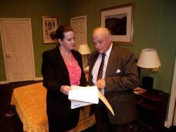 Accountant Karen Brown (Shirley Panek) shows Mayor Meekly (Ken Kienas) the irregularities in the city's financial records in her motel room during the police sting.