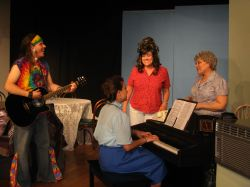 Harmony (Rodrigo Pool) plays the guitar with Lurlene on the piano (Grace Erdmann), Sara Lee (Holly Martin Czuchna), and Mama Wheelis (Sherry Bendt)