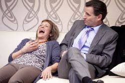 Veronica Novak (Naomi Jacobson) laughs as she may have had one too many, as Alan Raleigh (Paul Morella) looks on.