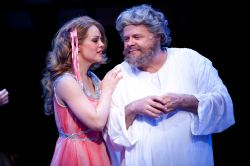 The Greek Muse Clio (Erin Weaver) tries to get on the good side of the Almighty Zeus (Harry A. Winter)