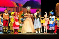 Glinda the Good Witch (Corrieanne Stein) and Dorothy (Kayli Modell) with the Munchkins