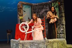 Evilina (Brandi Moore) tricks Princess Briar Rose (Maggie Keane) with the curse of the spinning wheel
