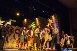The Poor of Urinetown stand behind Little Sally (Alex Poirier) and Bobby Strong (Drew Hare) as they lead the rebellion against higher public amenity fees in the 'Act 1 Finale'