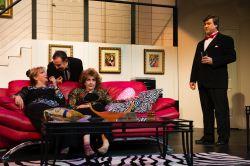 Claire Ganz (Jina Ames) and Chris Gorman (Ruth Neaveill) gossip rumors while Lenny Ganz (Chuck Dluhy) and Ken Gorman (Tom Flatt) listen in disbelief.
