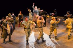 Kathleen Turner (center) as Mother Courage and the cast